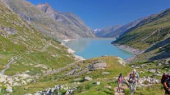 Group ascending a mountain on the Tour de Monte Rosa Walk above a stunning alpine lake | Andrew Bain