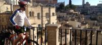 Cyclist viewing the historic cave dwellings in the Sassi di Matera | Kate Baker