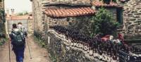 Pilgrims hiking through small village on the Camino | @timcharody