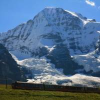 Train travel in the Swiss Alps bring spectacular views, here with Monch in the backdrop